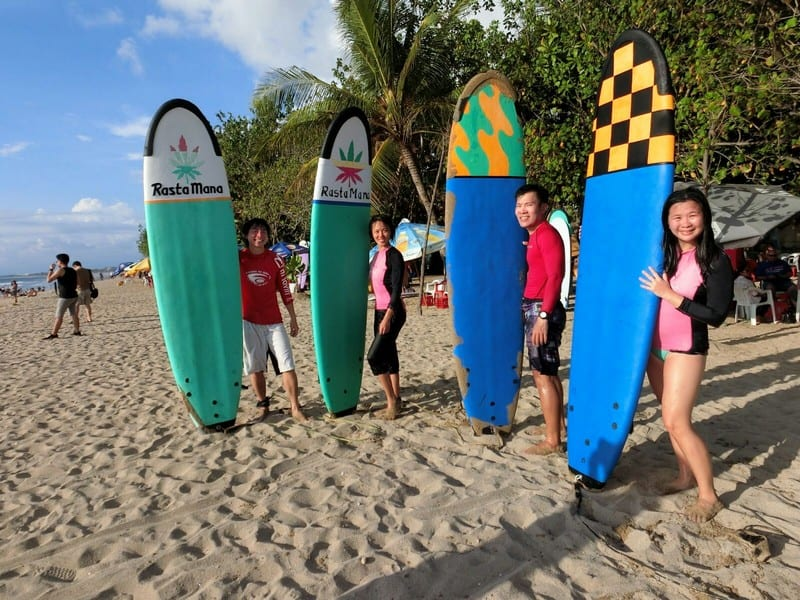 outdoor adventures in Bali - Kuta Beach at Bali Indonesia | We and our big colourful boards. Behind those smiles are exhausted aching bodies and nose and mouth full of saltwater