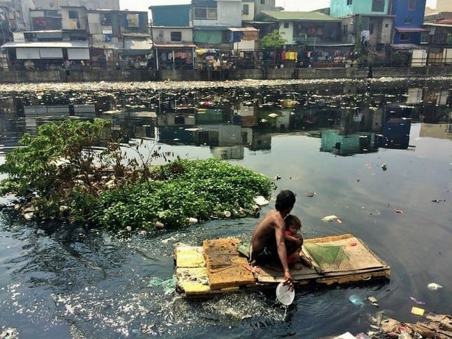 A father and child paddling out to seek and hope to find for something valuable | Slums in Manila
