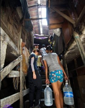 Carrying water back to the slums