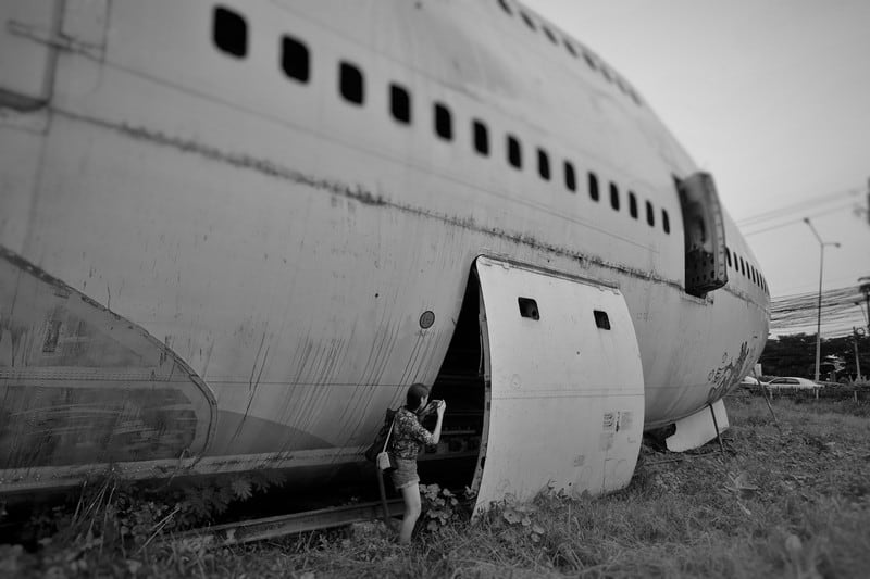 Peering into the plane to try to see if everything is still intact. Feels a bit like a sci fi movie scene! Abandoned airplane Graveyard hidden in Bangkok | Airplane Pictures Behind the scenes