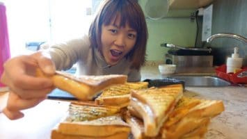 Greedy shot of me grabbing those freshly made toasties with tomato and cheese at Good Morning Hostel