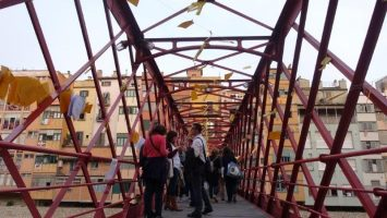 The famous red bridge of Girona, lined with yellow papers with poems