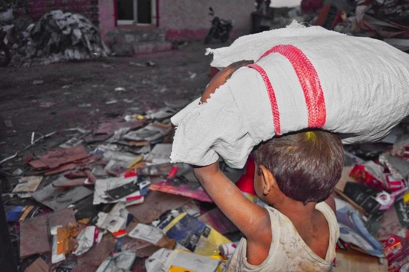 Child carrying laundry through field of trash