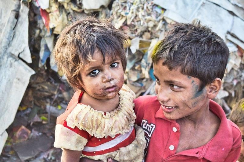 "Two children embracing one another after ""playing"" in their trash-filled slum area"