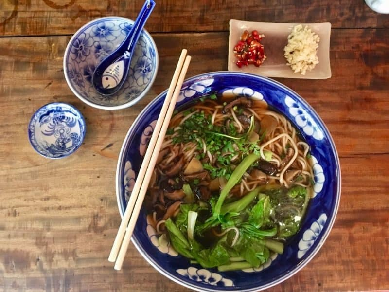 Bok choy, shiitake noodle soup in ceramic dishes